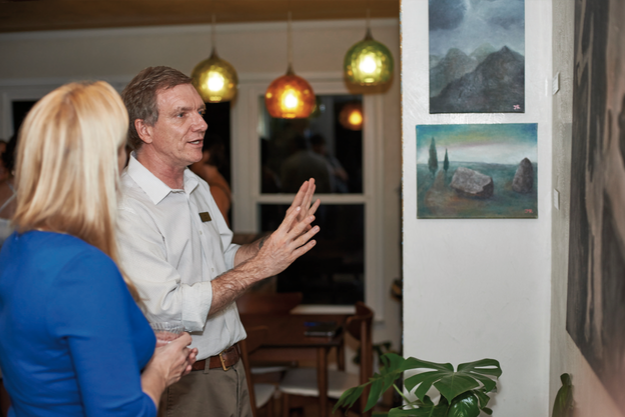 Curator, Boris Douglas Garbe, elaborates on a work at the house show of artist Jose M. Rivas